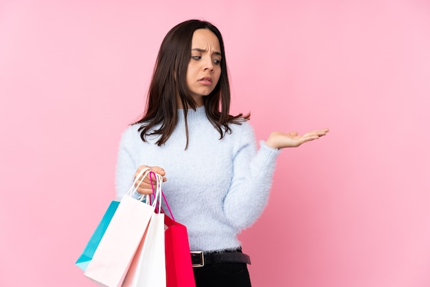 Young woman with shopping bag over isolated pink wall holding copyspace with doubts