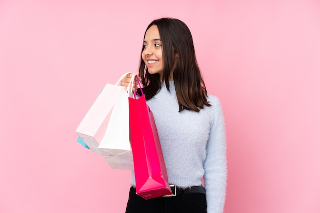 Young woman with shopping bag over isolated pink wall looking side