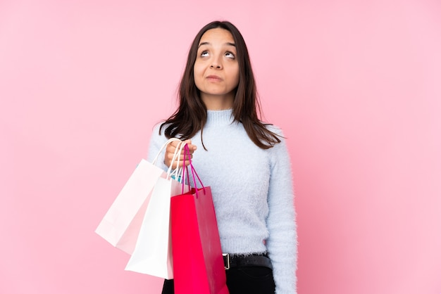 Young woman with shopping bag over isolated pink wall and looking up