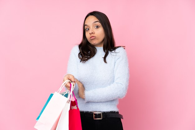 Young woman with shopping bag over isolated pink wall making doubts gesture while lifting the shoulders