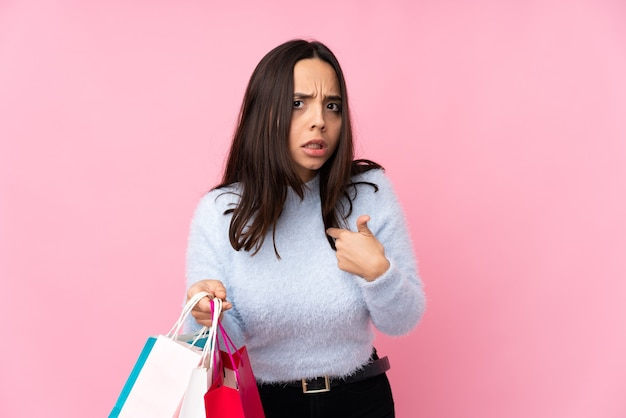 Young woman with shopping bag over isolated pink wall pointing to oneself