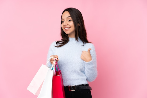Young woman with shopping bag over isolated pink wall proud and self-satisfied