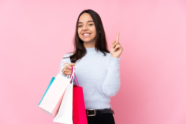 Young woman with shopping bag over isolated pink wall showing and lifting a finger in sign of the best