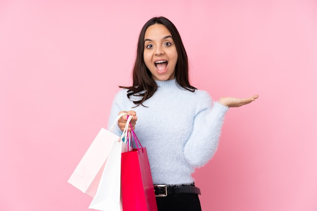 Young woman with shopping bag over isolated pink wall with shocked facial expression