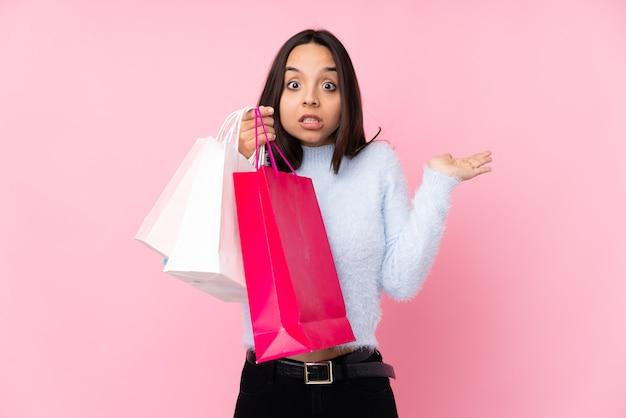 手を上げている間疑いを持っている孤立したピンクの買い物袋を持つ若い女性