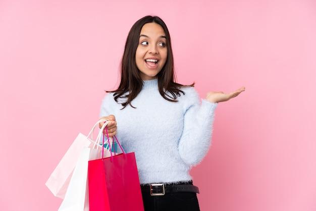 両手でコピースペースを保持している孤立したピンクのショッピングバッグを持つ若い女性