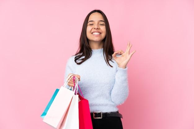 禅のポーズで孤立したピンクのショッピングバッグを持つ若い女性