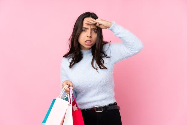 何かを探すために手で遠くを見ている孤立したピンクの買い物袋を持つ若い女性