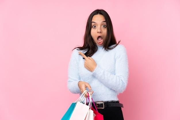 孤立したピンクの驚きとポインティング側に買い物袋を持つ若い女性