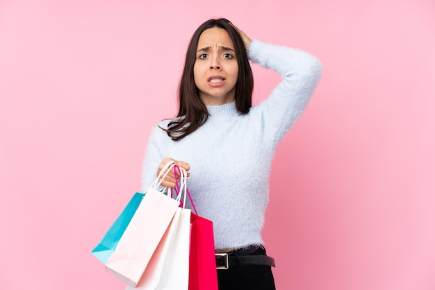 고립 된 분홍색 배경 위에 쇼핑백을 가진 젊은 여자는 좌절하고 머리에 손을 걸립니다