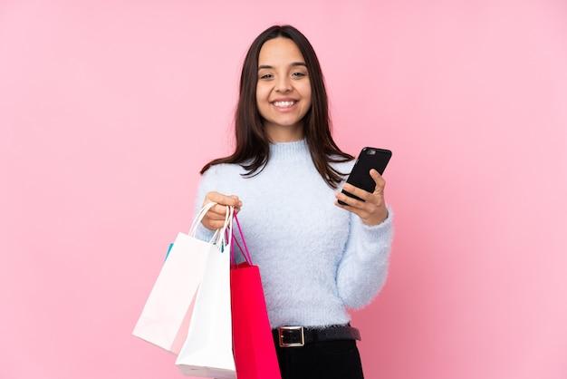 Молодая женщина с хозяйственной сумкой на изолированном розовом фоне держит кофе на вынос и мобильный