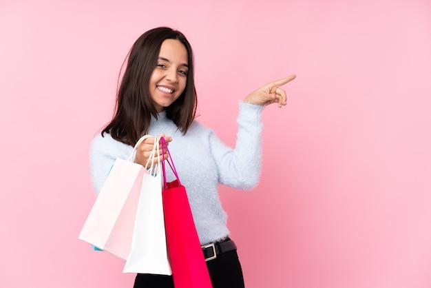 측면에 손가락을 가리키고 제품을 제시 고립 된 분홍색 배경 위에 쇼핑백을 가진 젊은 여자