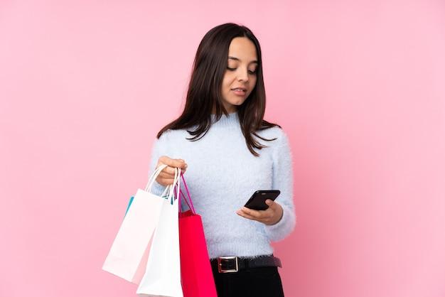 Молодая женщина с сумкой для покупок над изолированным розовым держит кофе на вынос и мобильный