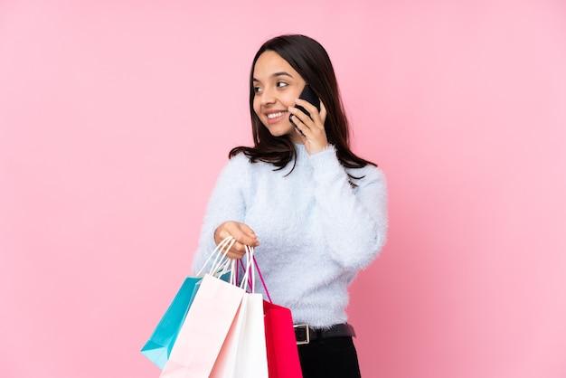 Молодая женщина с сумкой для покупок над изолированной розовой стеной держит кофе на вынос и мобильный