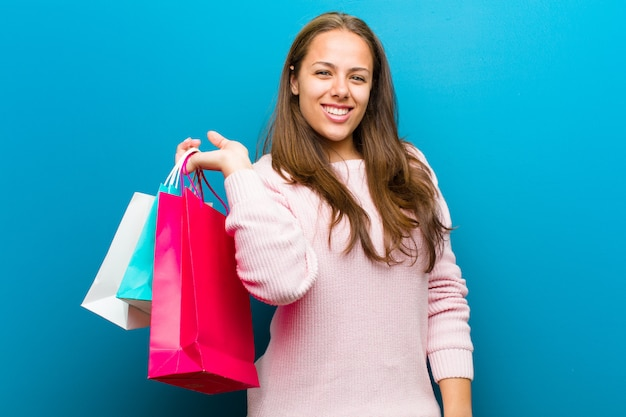 Young woman with shopping bags against blue background