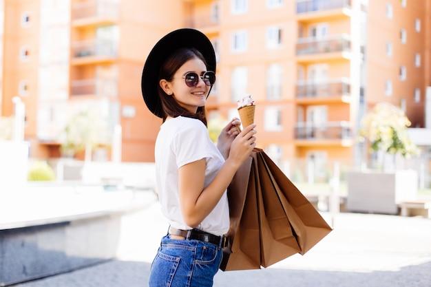 ショッピングバッグと街の通りにアイスクリームを持つ若い女性