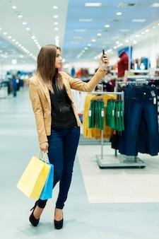 Молодая женщина с хозяйственными сумками и мобильным телефоном