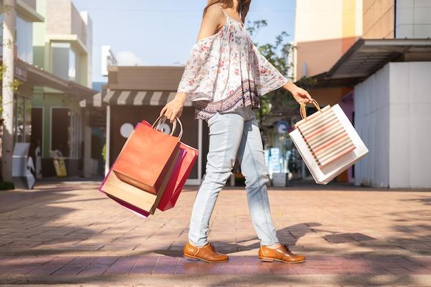 黒の金曜日にショッピングモールでショッピングバッグを持つ若い女性