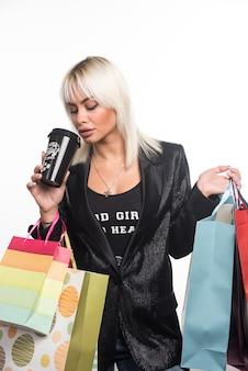 Giovane donna con i sacchetti della spesa che beve tazza di caffè su priorità bassa bianca. foto di alta qualità