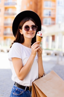 Young woman with shopping bags and ice cream on city street