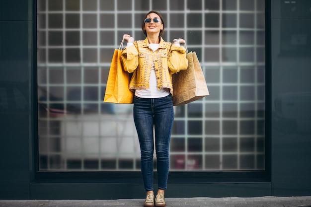 Молодая женщина с сумками в городе