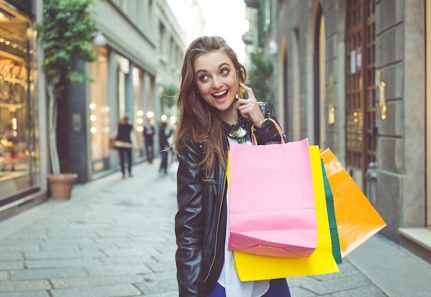 거리에서 쇼핑 가방을 가진 젊은 여자