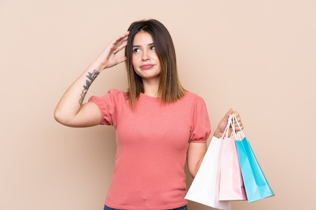 Young woman with shopping bags over isolated wall