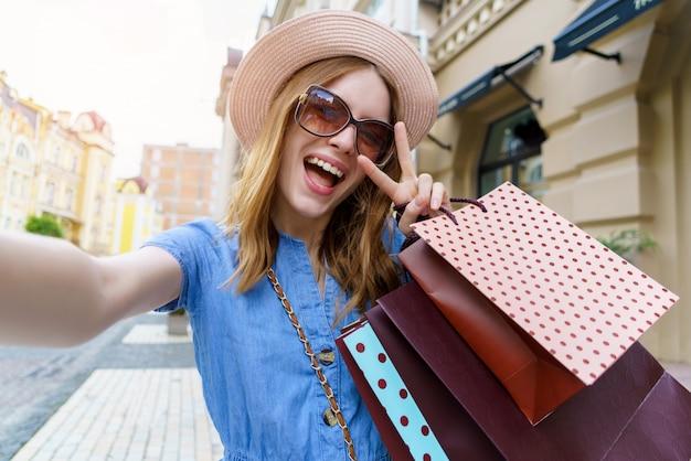 Молодая женщина с хозяйственными сумками делает селфи, гуляя по городу в летний день