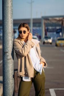 카메라에 포즈를 취하는 버스 정류장에 쇼핑백과 젊은 여자.
