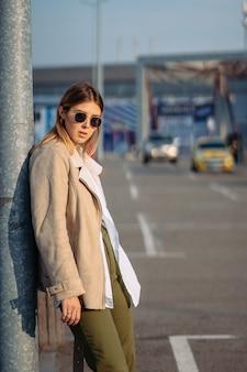 バス停のポーズで買い物袋を持つ若い女性