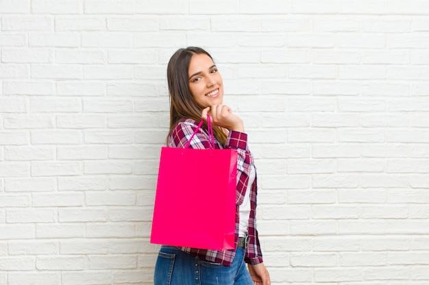 レンガの壁に買い物袋を持つ若い女