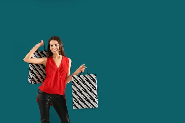 色の表面に買い物袋を持つ若い女性