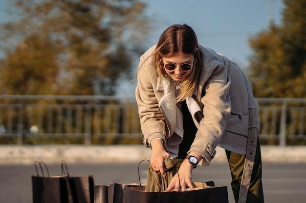 Молодая женщина с хозяйственными сумками на парковке