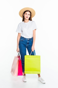 흰 벽에 쇼핑백을 가진 젊은 여자