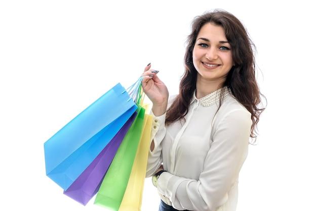 Молодая женщина с хозяйственными сумками на белой стене