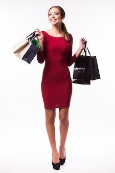 叫び、不思議に思って白い壁の上の買い物袋を持つ若い女性