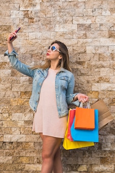 Young woman with shopping bags taking selfie