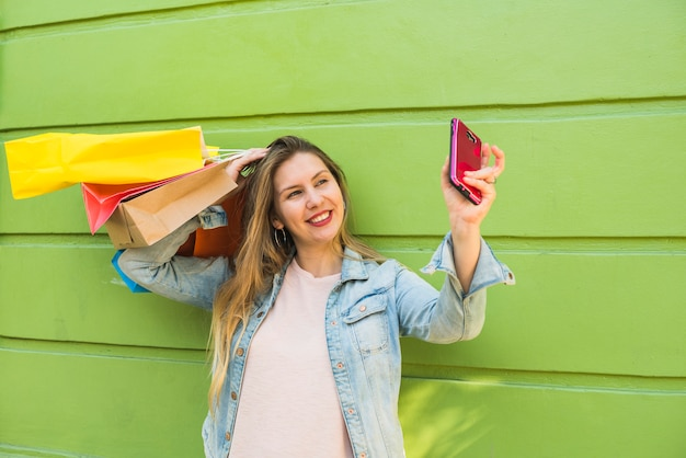 Selfieを取って買い物袋を持つ若い女