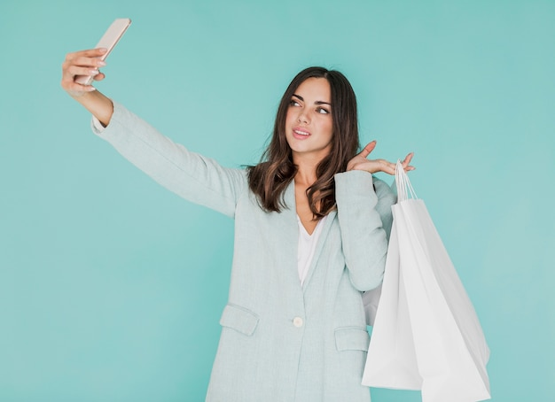 Young woman with shopping bags taking a selfie