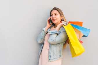 Young woman with shopping bags talking by phone