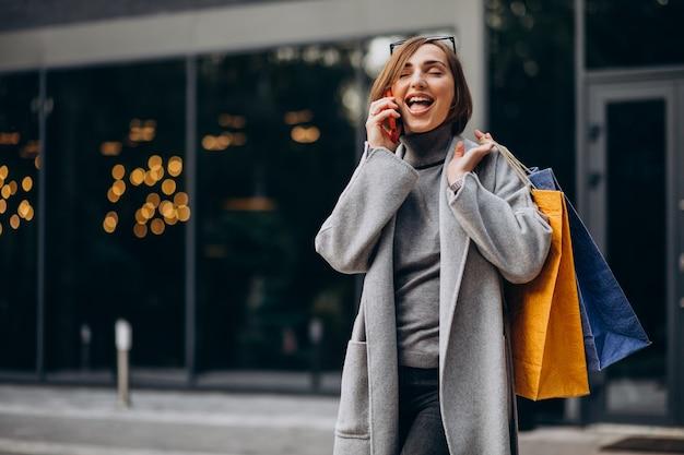 Молодая женщина с хозяйственными сумками разговаривает по телефону