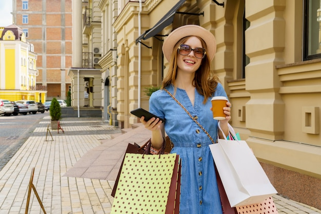 Young woman with shopping bags walking in a city at summer day