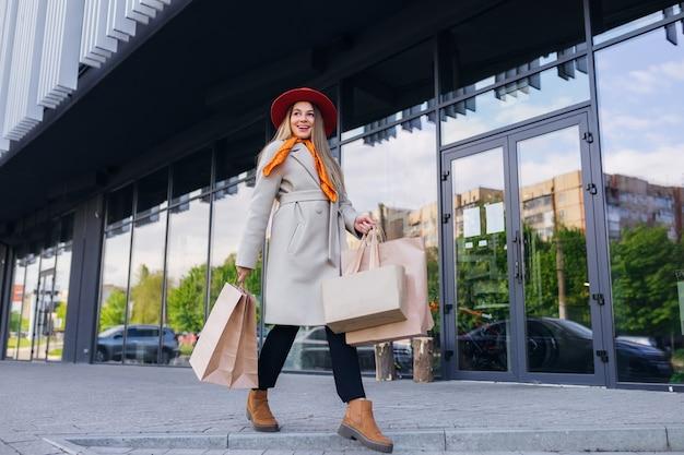 街の通りを歩いて買い物袋を持つ若い女性