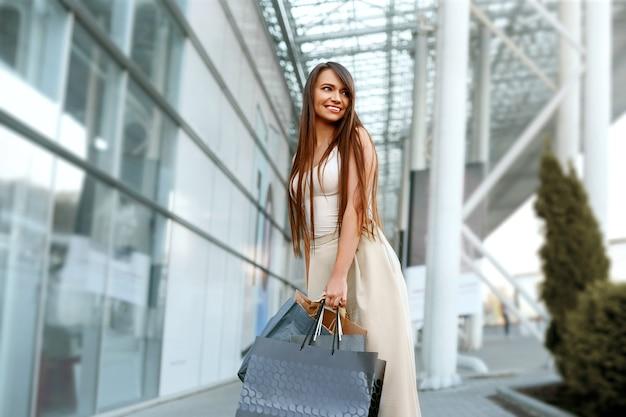 店から出て買い物袋を持つ若い女性
