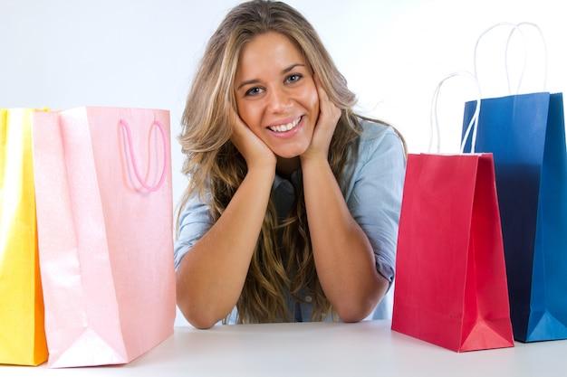 Giovane donna con borse della spesa su uno sfondo bianco