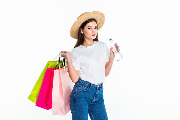 Young woman with shopping bags on white wall