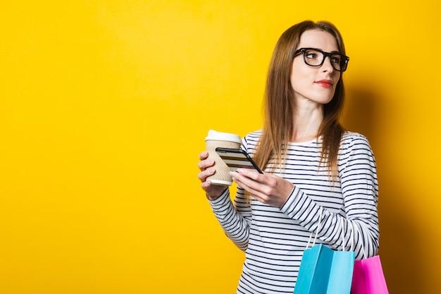 Молодая женщина с хозяйственными сумками с бумажным стаканчиком с кофе, глядя на телефон на желтом фоне