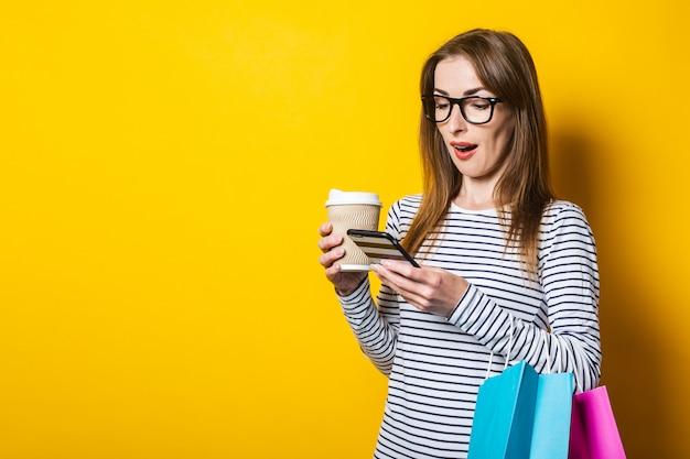 Молодая женщина с хозяйственными сумками, с бумажным стаканчиком с кофе удивленно смотрит в телефон на желтом фоне