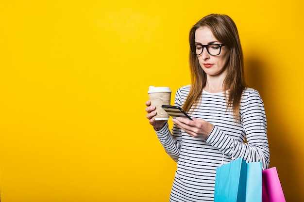 Young woman with shopping bags with a paper cup with coffee looks at the phone on a yellow background