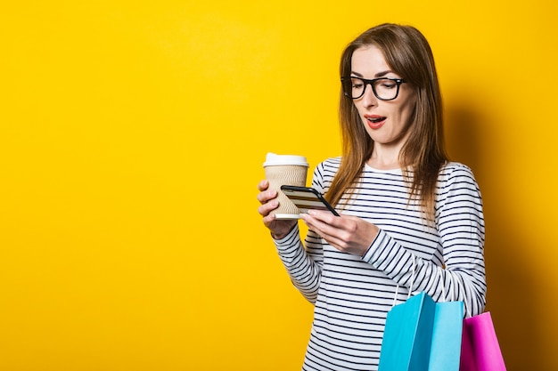 Young woman with shopping bags, with a paper cup with coffee, looks in surprise at the phone on a yellow background